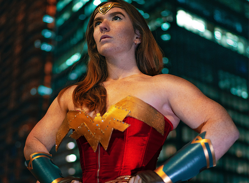 A strong person in a wonder woman costume looking off to the distance