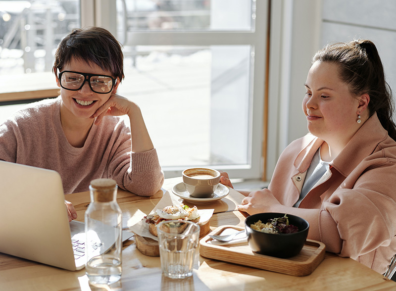 Two friends in pink having a morning tea with others online